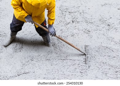 THESSALONIKI, GREECE - FEBRUARY 17, 2015: laborers throwing cement during upgrades Sidewalk on a rainy day in the streets of Thessaloniki