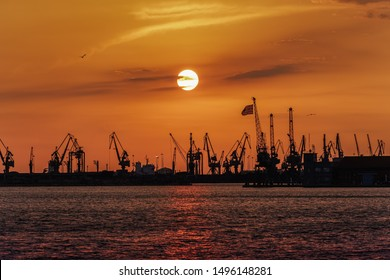 Thessaloniki, Greece golden hour sunset landscape at the city port. Orange sunset above low-rise port buildings, seen from the old waterfront area with port cranes and Greek flag waving.