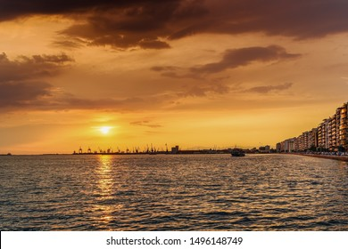 Thessaloniki, Greece golden hour sunset landscape at the city port with tourist ship sailing. Orange sunset above low-rise port & city buildings, with unidentified crowd along the old waterfront area.