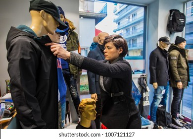 Thessaloniki, Greece - January 19, 2018: Woman decorates window showcase at a clothing store in the center of Thessaloniki in view of winter discounts.