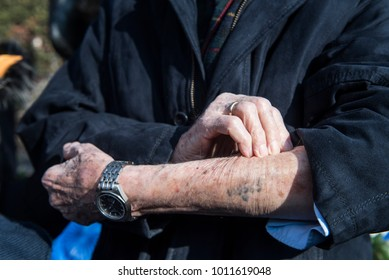 Thessaloniki, Greece - January 28, 2018. A Jewish Holocaust survivor, shows his arm tattoo in front of the Holocaust memorial during a ceremony commemorating the Jewish persecution during WWII.