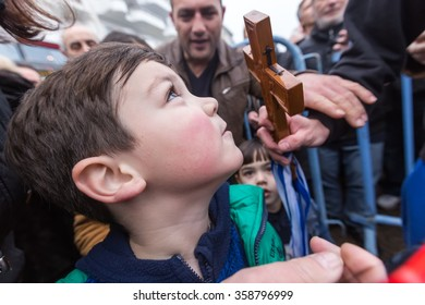 Thessaloniki, Greece, January 6, 2016: A child kisses a wooden cross retrieved from the sea during the blessing of the water ceremony marking the Orthodox Epiphany Day