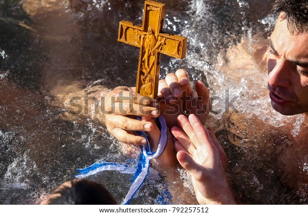 Thessaloniki, Greece, January 6, 2018: A swimmer kisses a wooden cross retrieved from the sea, during the blessing of the water ceremony marking the Orthodox Epiphany Day, in port of Thessaloniki