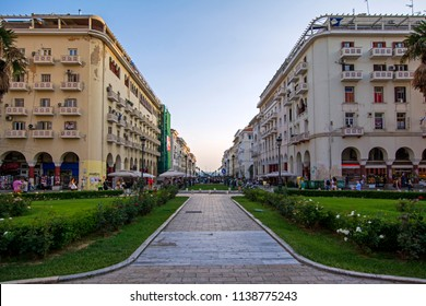 Thessaloniki, Greece - July 06, 2018: Wide angle perspective view of Aristotelous Alley with classical buildings and green lawns at the sunset