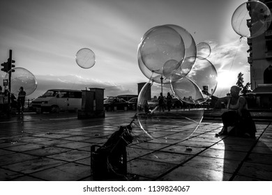 Thessaloniki, Greece - July 06, 2018: Contrast scene with woman sellingballoons with electric lights against the beautiful sunset background on Aristotelous Square. Black and white photography