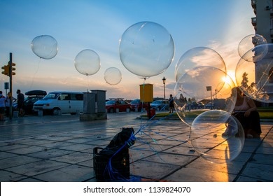 Thessaloniki, Greece - July 06, 2018: Contrast scene with woman sellingballoons with electric lights against the beautiful sunset background on Aristotelous Square