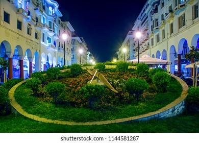 Thessaloniki, Greece - July 06, 2018: Night cityscape with huge clock on green lawn at Aristotelous Alley