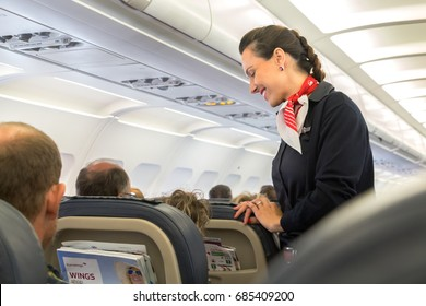 Thessaloniki , Greece - July 16, 2017: A female flight attendant  is speaking with a passenger sitting in the economy class of the route Thessaloniki - Múnich of Eurowings Airline.