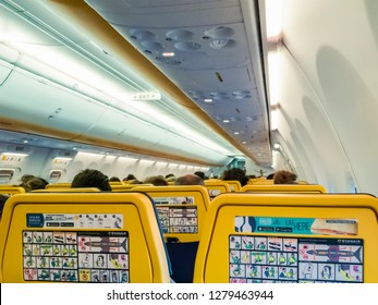 Thessaloniki, Greece - July 16 2018: Ryanair aircraft seats view with passengers.Rear view of new seats thinner layout inside a Ryanair Boeing 737 800 aircraft with safety info cards displayed.