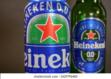 Thessaloniki, Greece - June 16 2019: Heineken zero alcohol 330 ml beer can. Non-alcoholic lager beer on 33cl can with water droplets on black background with blurred zero beer glass bottle.