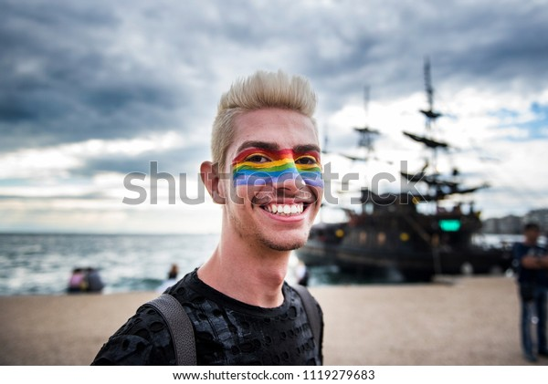 Thessaloniki, Greece - June 23, 2018. A man with his face painted in the colors of the Rainbow Flag takes part at the annual Gay Pride.