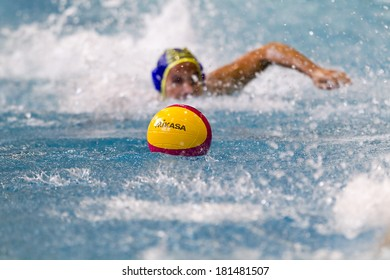 THESSALONIKI, GREECE MAR 5, 2014 : A player swimming towards the ball during the Greek League water polo game PAOK vs Nereas on March 5, 2014. Focus is on the ball.