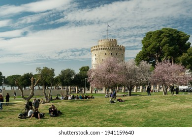 Thessaloniki, Greece March - 13 2021: Unidentified crowd on a park before the White Tower. People at the park before the city landmark on a spring day, with bloomed cherry blossom trees.