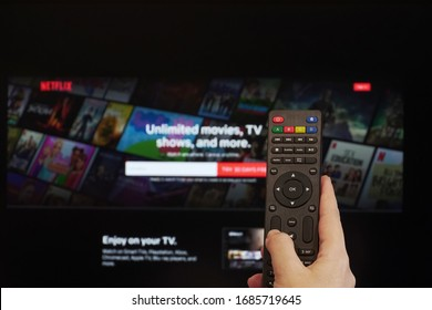 Thessaloniki, Greece - March 21 2020: Netflix streaming Service VoD content provider concept. Hand holds a multimedia remote control before a screen with Netflix app online watch login page.