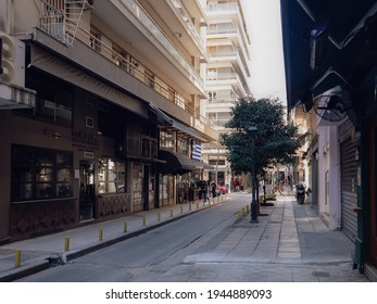 Thessaloniki, Greece - March 27 2021: Customers outside take-away working bar due to covid-19 restrictions. Hellenic crowd on the pavement buy their beverage from a store with a big Greek flag above.