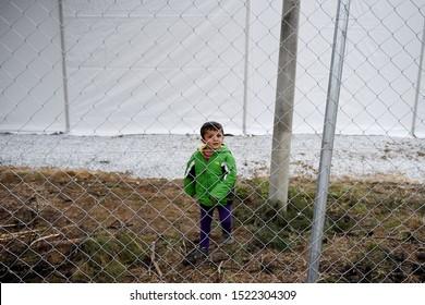 Thessaloniki, Greece - March 4, 2016. A refugee boy stands behind a fence inside a refugee camp.