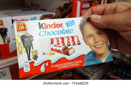 THESSALONIKI, GREECE - November 09, 2017: Hand with Kinder chocolate bars on supermarket. Kinder bars are produced by Italian confectionery multinational Ferrero SpA.