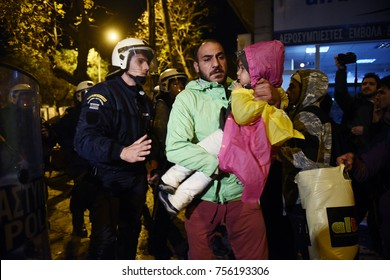 Thessaloniki, Greece - November 15, 2017. A man holds his child in front of a police blockade, as refugees try to march from Thessaloniki to the Greek - Macedonian border.