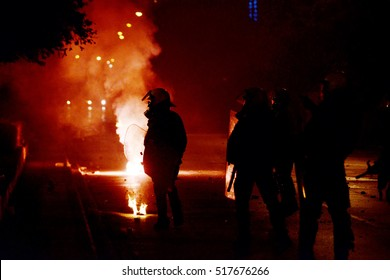 Thessaloniki, Greece - November 17, 2016. Greek police officers stand, as protesters throw firebombs to them, during the annual commemoration of 1973 student uprising against the military dictatorship