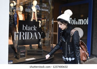Thessaloniki, Greece - November 22, 2018. A young woman walks past a clothes shop with a poster promoting Black Friday deals.