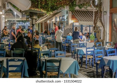 Thessaloniki, Greece - October 12 2019: Hellenic nightlife scene of people at outdoors tavern restaurants. Unidentified crowd eating & drinking at tavernas in the center at Athonos area.