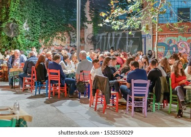 Thessaloniki, Greece - October 12 2019: Hellenic nightlife scene of people at outdoors tavern restaurants. Unidentified crowd eating & drinking at tavernas in the center at Ano Ladadika area.
