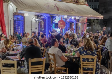 Thessaloniki, Greece - October 12 2019: Hellenic nightlife video of people at outdoors tavern restaurants. Crowd eating & drinking at illuminated taverna with live bouzouki music at Ladadika area.