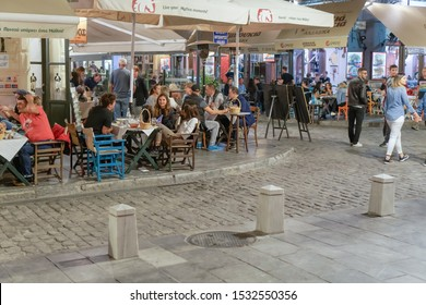 Thessaloniki, Greece - October 12 2019: Hellenic nightlife scene of people at outdoors tavern restaurants. Unidentified crowd eating & drinking at tavernas in the center at Ladadika area.