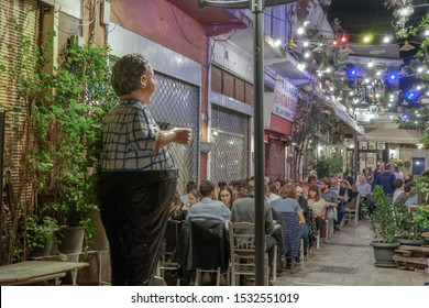 Thessaloniki, Greece - October 12 2019: Hellenic nightlife scene of people at outdoors tavern restaurants. Unidentified crowd eating & drinking at tavernas in the center at Bezesteni area.