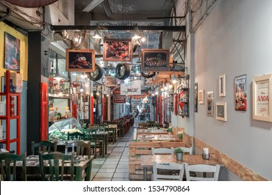 Thessaloniki, Greece - October 16 2019: Hellenic nightlife scene of empty indoors tavern restaurants. Empty tavernas chairs and tables without crowd in the center at Modiano area.