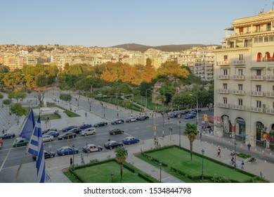Thessaloniki, Greece - October 16 2019: Upper Town & Aristotelous square at golden hour. Ano Poli UNESCO Heritage district with Byzantine castles visible from Aristotelous Square with traffic & taxis.