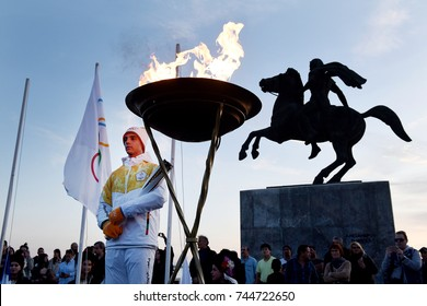 Thessaloniki, Greece - October 27, 2017. A Greek athlete lights stands next to the Olympic Flame of Pyeongchang 2018 Winter Olympics, in front of the Alexander the Great Statue.