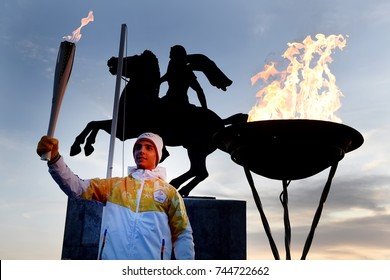Thessaloniki, Greece - October 27, 2017. A Greek athlete lights the Olympic Flame of Pyeongchang 2018 Winter Olympics, after its arrival in the city, in front of the Alexander the Great Statue.
