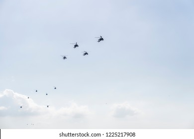 Thessaloniki, Greece - October 28 2018: Greek Air Force helicopters flying. Helicopters like Boeing AH-64 Apache attack, Boeing CH-47 Chinook lift and Bell utility ones at military parade.