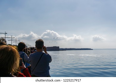Thessaloniki, Greece - October 28 2018: Greek Air Force helicopters flying. Unidentified crowd observing Boeing AH-64 attack helicopters and Boeing CH-47 Chinook lift helicopters at military parade.