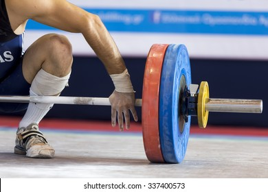 Thessaloniki, Greece, October 3, 2015: Hands and feet athlete on the barbell. Young athlete preparing to lift weights during the Greek Weightlifting Championship