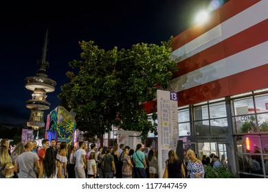 Thessaloniki, Greece - September 10 2018: Visitors of 83rd International Fair outside a pavilion. Night view of people entering USA pavilion with background view of OTE telecommunications tower.