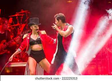 THESSALONIKI, GREECE, SEPTEMBER 11, 2014: Singer Sakis Rouvas performing at MAD North Stage festival by Thessaloniki International Fair. Blur stage spotlights with laser rays in the background.