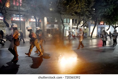 Thessaloniki, Greece - September 18, 2017. Police officers run as anarchists clash with them, during a violent antifascist protest in memory of the Greek rap singer Pavlos Fyssas.