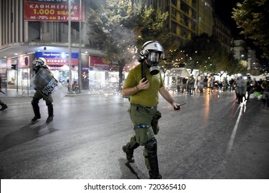 Thessaloniki, Greece - September 18, 2017. Police officers try to avoid fireworks thrown by anarchists during a violent antifascist protest in memory of the Greek rap singer Pavlos Fyssas.