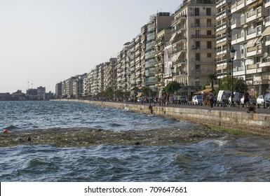 Thessaloniki, Greece - September 2 2017: Thermaic Gulf water pollution. Sea pollution on the waterfront before the White Tower, the city landmark, while people walk along the promenade.