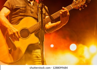 Thessaloniki, Greece - September 22, 2018: acoustic guitar in action on stage performing at a rock concert at the open theater of the city, blur stage spotlight with laser rays.