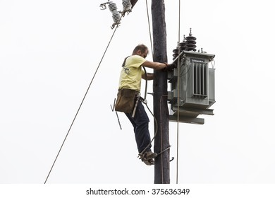 Thessaloniki, Greece- September 24, 2015: Worker climbing on Electrical concrete pole transmission line tower in Thessaloniki, Greece.