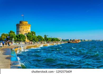 THESSALONIKI, GREECE, SEPTEMBER 8, 2017:  People are walking on a seaside promenade towards the white tower in Thessaloniki, Greece