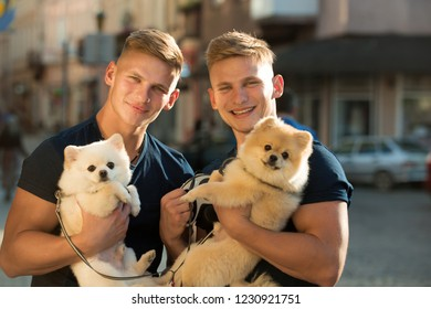 They belong together. Happy family on walk. Twins men hold pedigree dogs. Muscular men with dog pets. Happy twins with muscular look. Spitz dogs love the company of their family.