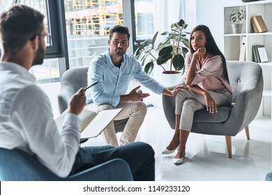 They need an advice. Young married couple talking while sitting on the therapy session with psychologist
