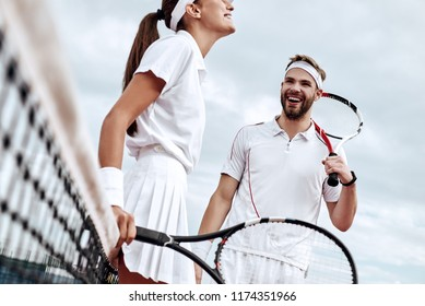 They play like a team. Beautiful young woman and man holding tennis racket and discussing set