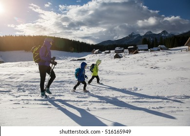 They say there are is no bad weather, just bad clothing. Kids are enjoying winter elements with their parents. Concept photo of children growing up with nature.