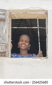 THIAROYE, SENEGAL, AFRICA, JULY 18, 2014, Unidentified woman standing by the window of her house