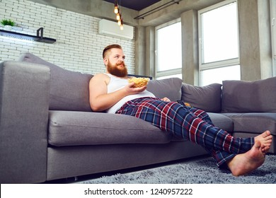 Thick bearded man eating popcor sitting on the couch.